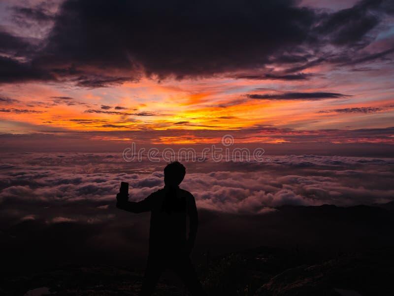 De silhouetmensen nemen een Selfie op de klip met mooie zonsopganghemel op de berg van Khao Luang stock afbeeldingen