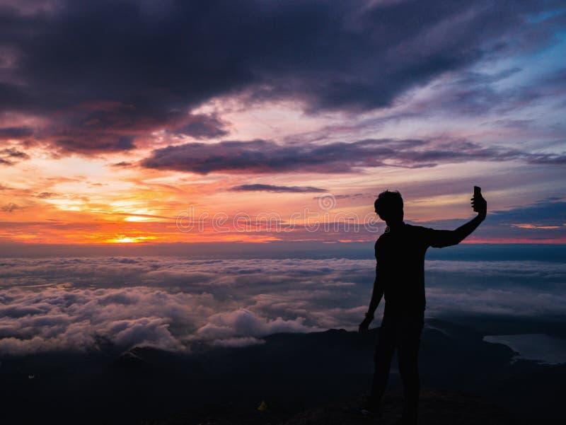 De silhouetmensen nemen een Selfie op de klip met mooie zonsopganghemel op de berg van Khao Luang royalty-vrije stock foto
