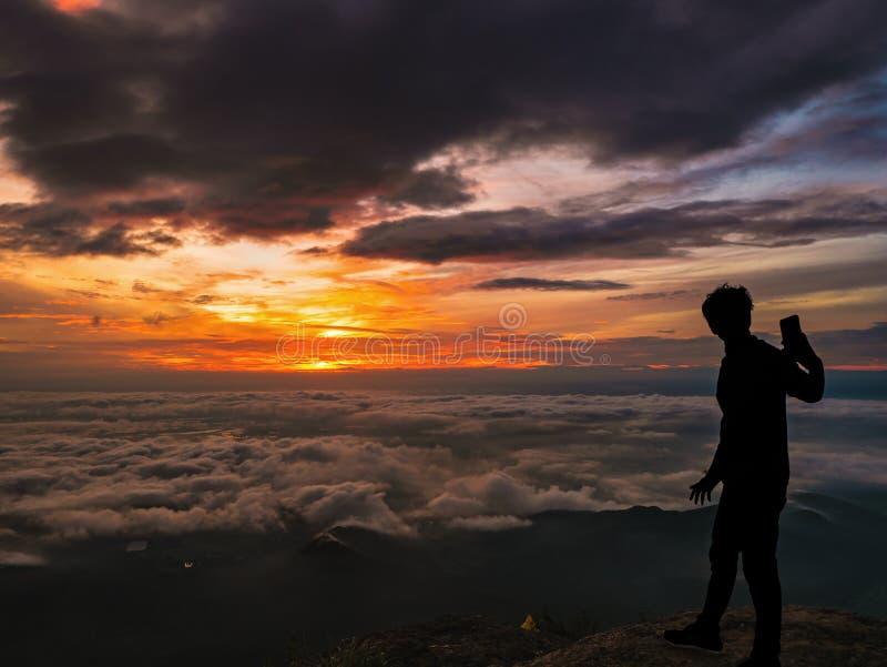 De silhouetmensen nemen een Selfie op de klip met mooie zonsopganghemel op de berg van Khao Luang stock foto
