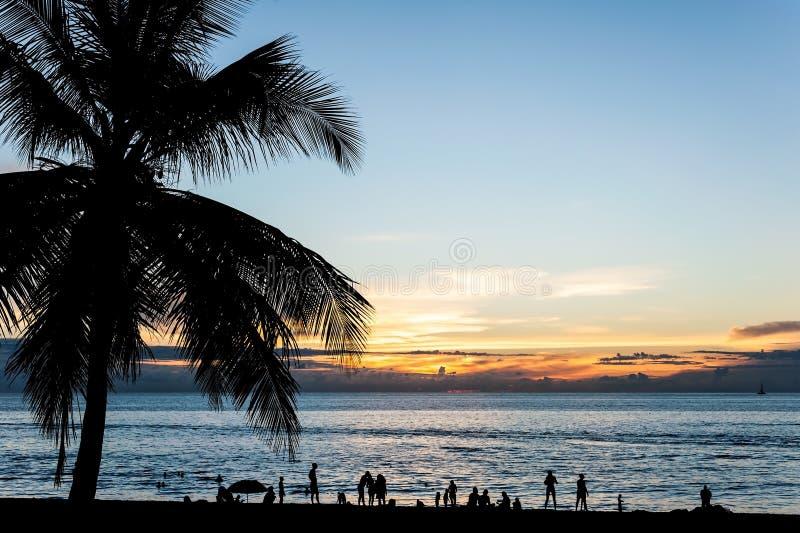 De silhouetmensen ontspannen op het strand met kleur van zonsondergang stock afbeelding
