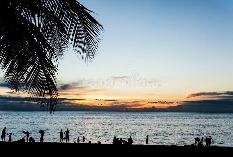 De silhouetmensen ontspannen op het strand met kleur van zonsondergang royalty-vrije stock afbeelding