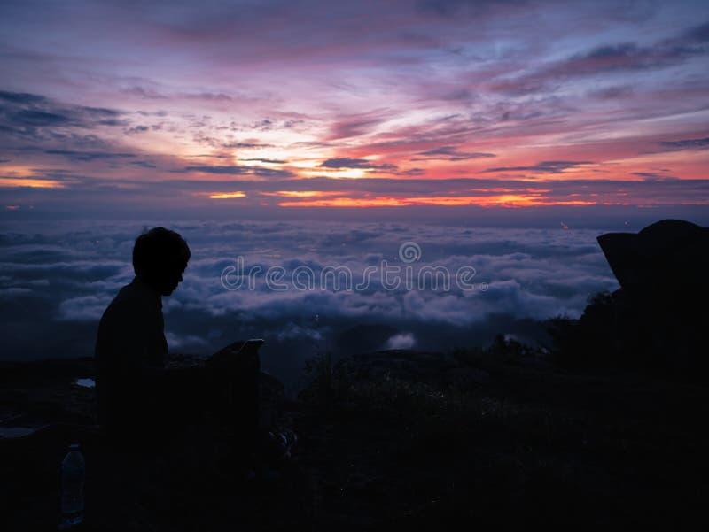 De silhouetmensen zitten op de klip met mooie zonsopganghemel op de berg van Khao Luang in het Nationale Park van Ramkhamhaeng royalty-vrije stock foto's