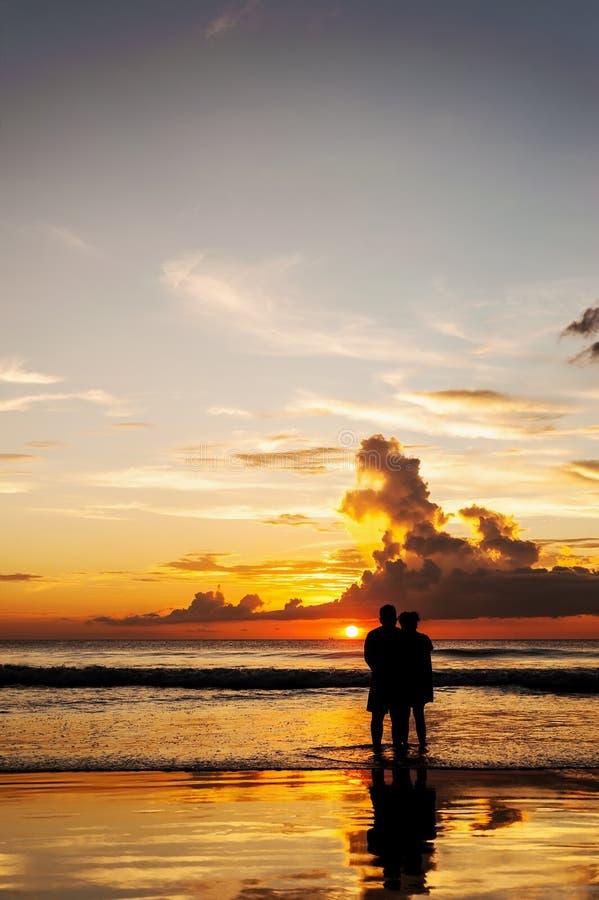 De silhouetminnaars ontspannen op het strand in kleur van zonsondergang stock afbeelding