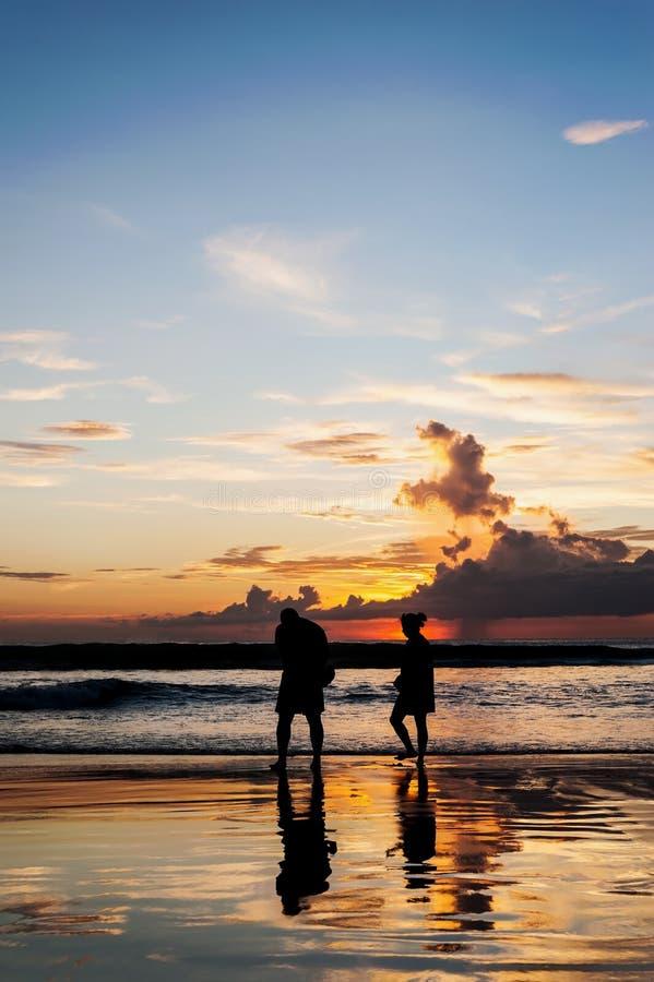 De silhouetminnaars ontspannen op het strand in kleur van zonsondergang stock afbeeldingen