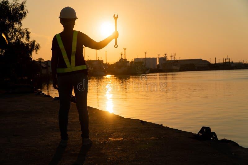 De silhouetten van Aziatische de holding van de vrouweningenieur moersleutels en status op scheepswerf en achtergrond is de silo  stock foto