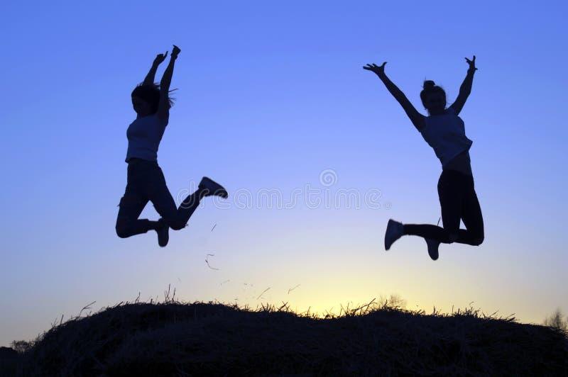 De silhouetten van de twee meisjes schilderden het springen af stock foto