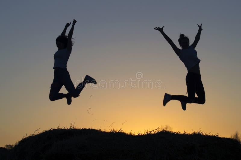 De silhouetten van de twee meisjes schilderden het springen af royalty-vrije stock afbeeldingen