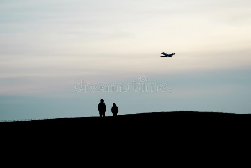 De silhouetten van twee mensen bevinden zich op een hoge heuvel en letten op een vliegtuig vliegend hoog in de hemel royalty-vrije stock foto
