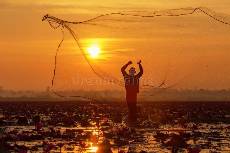 De silhouetvisser die aan de boot in meer voor catchin werken stock afbeelding