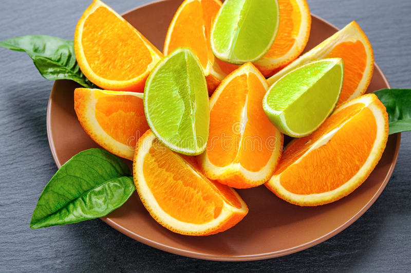 De sinaasappel en de kalk sneden segmenten met groene bladeren op bruine plaat, zwarte leisteen Vitamineconcept royalty-vrije stock afbeelding