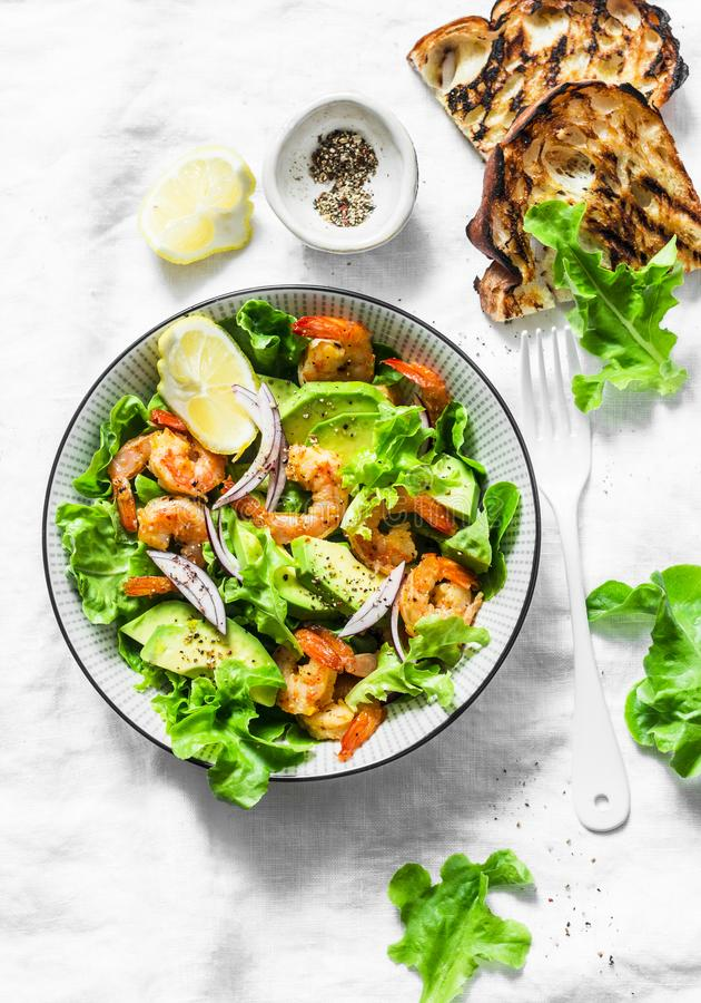 De sinaasappel marineerde garnalen, avocado, de salade van tuinkruiden - heerlijke gezonde snack, voorgerechten, tapas op een lic royalty-vrije stock foto