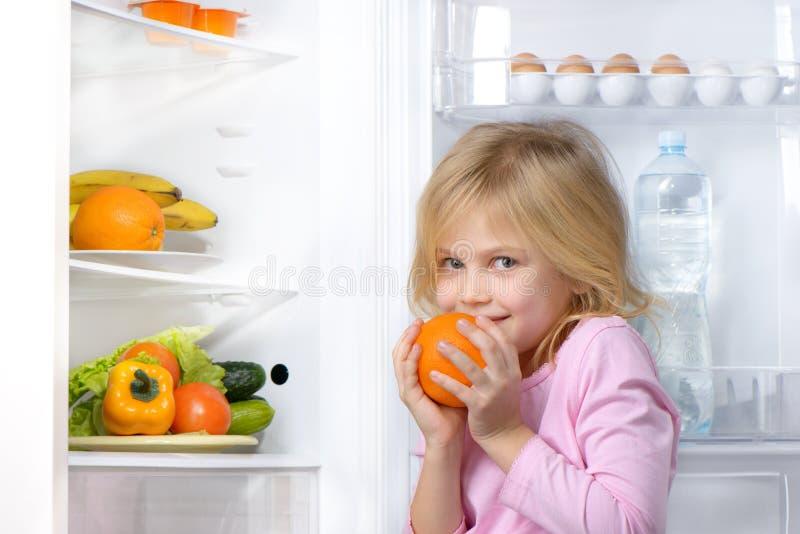 De sinaasappel van de meisjeholding dichtbij open koelkast stock afbeelding