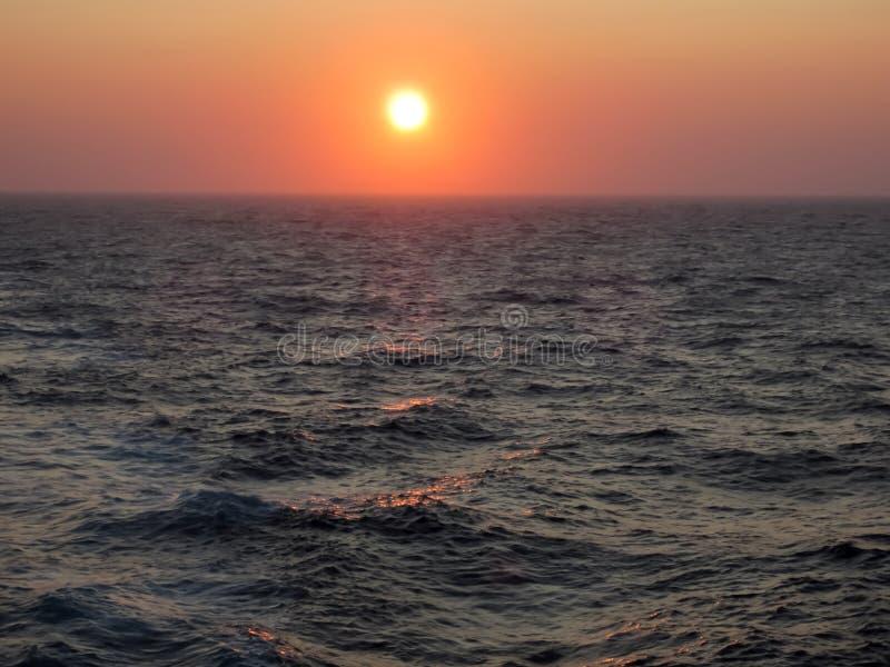 De Sinaasappel van zonsonderganggloed over Ruwe Oceaanoppervlakte royalty-vrije stock foto's