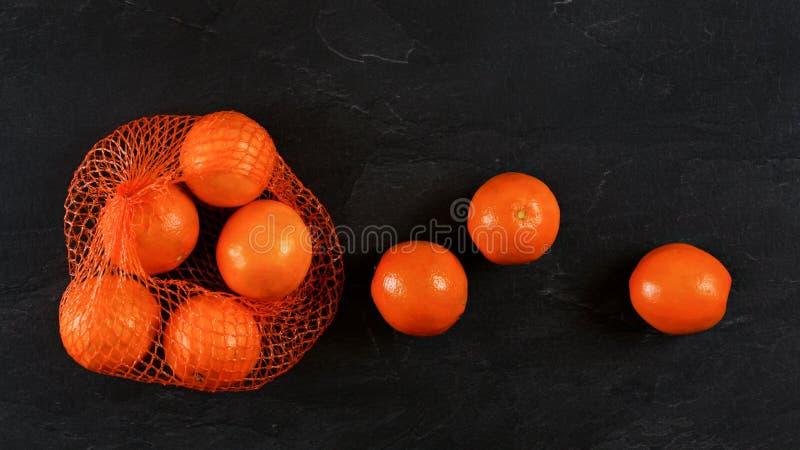 De sinaasappelen in netto, wat verspreid op zwarte steen zoals raad, vlakte leggen foto royalty-vrije stock fotografie