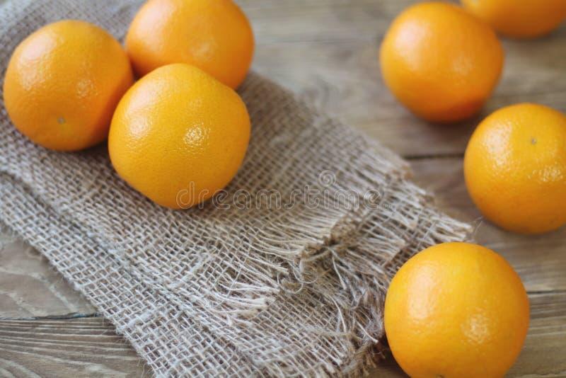 De sinaasappelen zijn helder oranje kleurenclose-up op de rechterkant van het kader op een oude houten achtergrond royalty-vrije stock fotografie