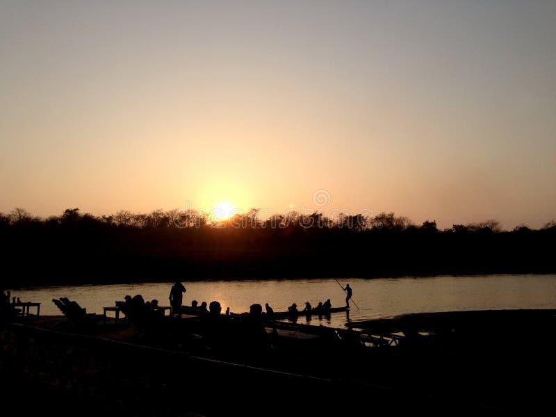 De sista fartygen som går tillbaka från den Chitwan nationalparkNepal solnedgången arkivfoto