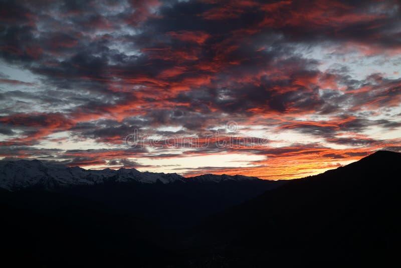 De sista strålarna av solen bakifrån de upplysta molnen för berg i overkliga härliga färger royaltyfria foton
