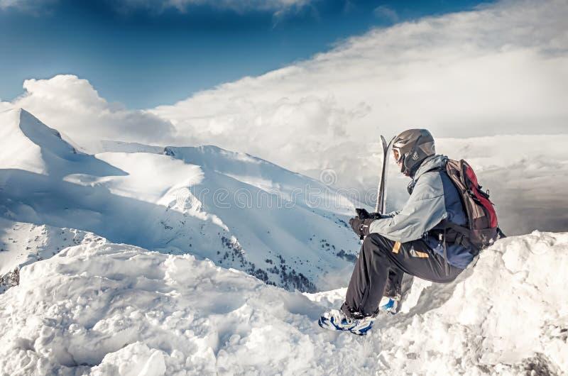De skiër zit met skis op grote rots op bergenachtergrond Bansko, Bulgarije royalty-vrije stock foto's