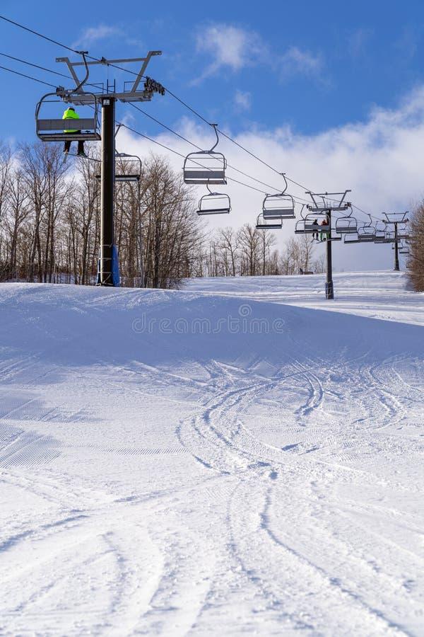 De skiërs berijden omhoog een stoeltjeslift boven een onlangs verzorgde skilooppas royalty-vrije stock afbeeldingen
