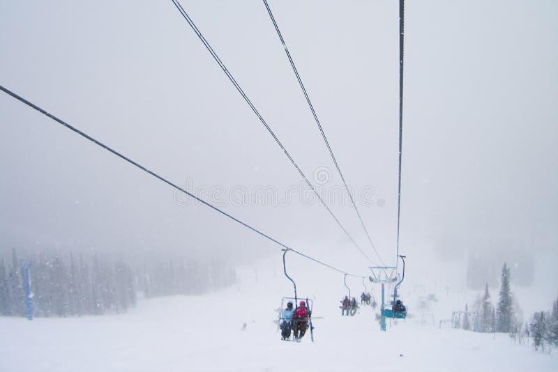 De skiërs op de stoeltjeslift leiden terwijl sneeuwval stock foto's