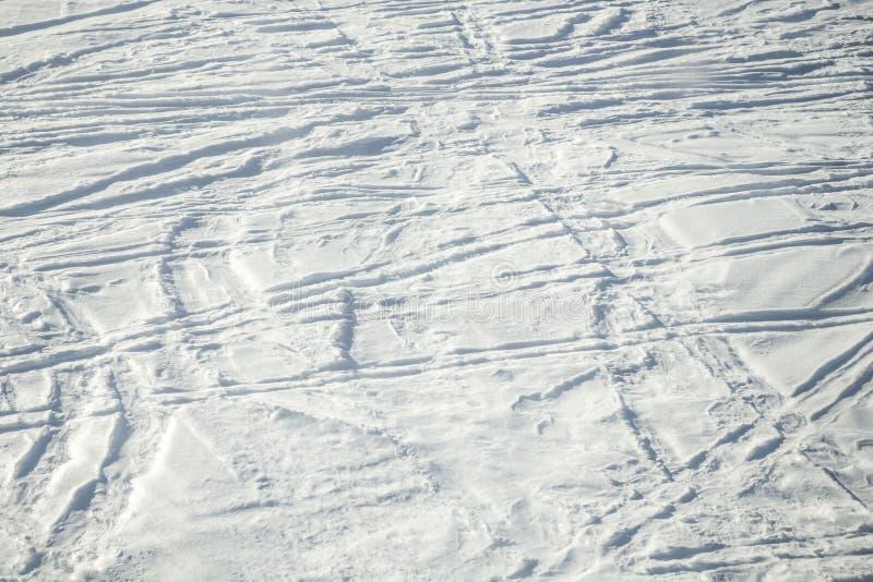 De ski sleept en volgt textuur in verse sneeuw Zonnige dag achtergrond met exemplaarruimte voor tekst stock foto