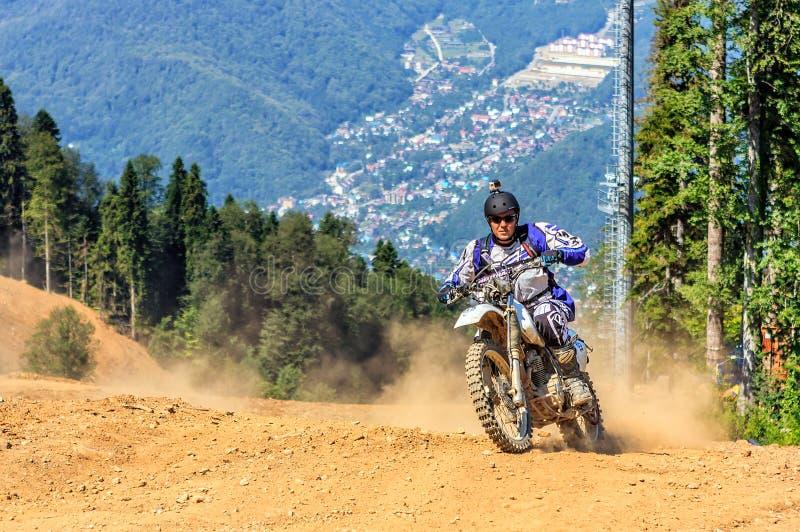 De skisporen van de bergtoevlucht van Sotchi dienen als terreinstegen voor enduromotocross in de zomer De mens berijdt motor met  stock foto