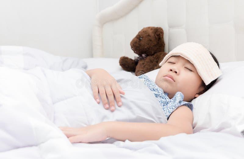 De slaap en de zieken van het jong geitjemeisje op het bed met koelere zakdoek o royalty-vrije stock fotografie