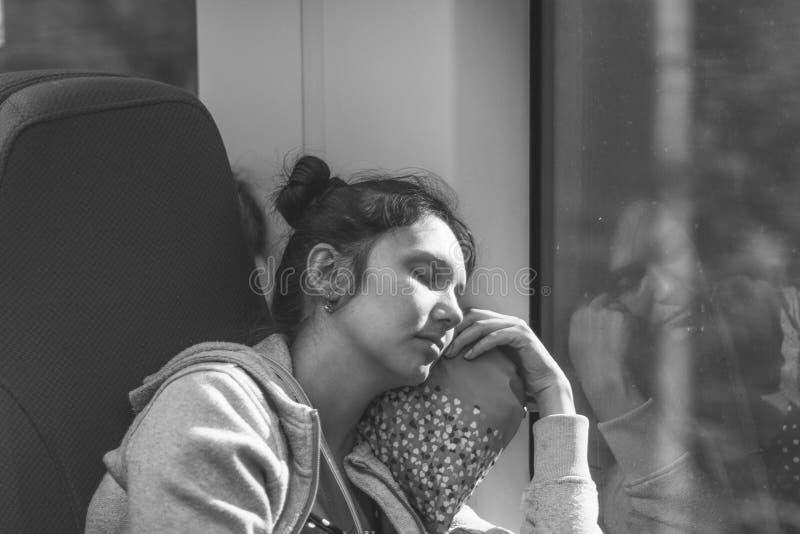 De slaap jonge vrouw die in hoge snelheids elektrische trein Lastochka berijden in de zomer, zwart-witte foto royalty-vrije stock afbeelding