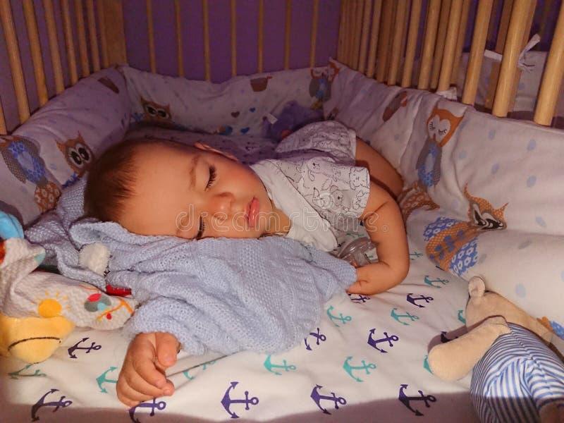 De slaap van de babyjongen - slaappositie stock afbeelding