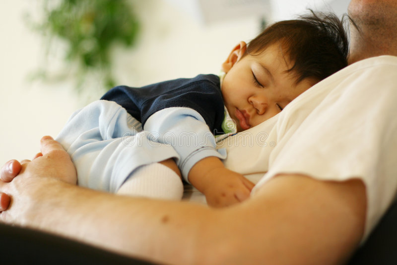 De slaap van de baby op de borst van de papa