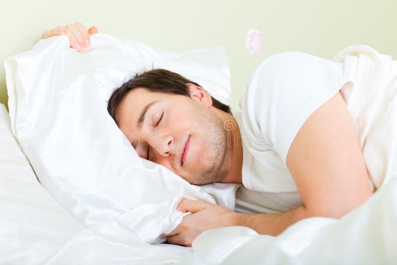 De slaap van de mens in bed stock afbeelding