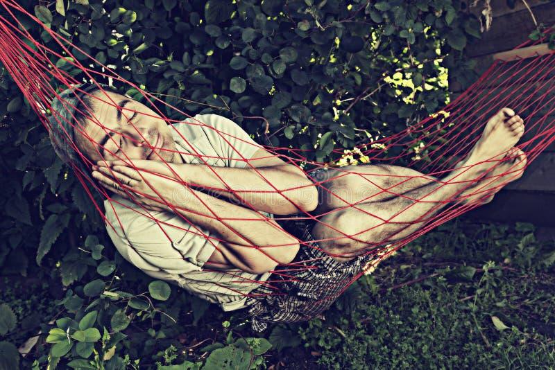 De slaap van de mens in hangmat stock afbeelding