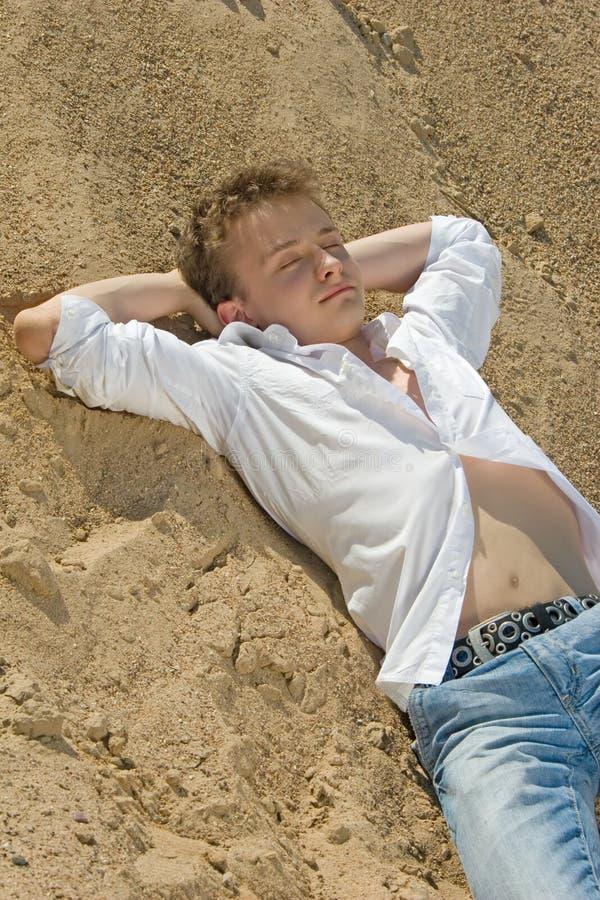 De slaap van de mens op zand stock afbeelding