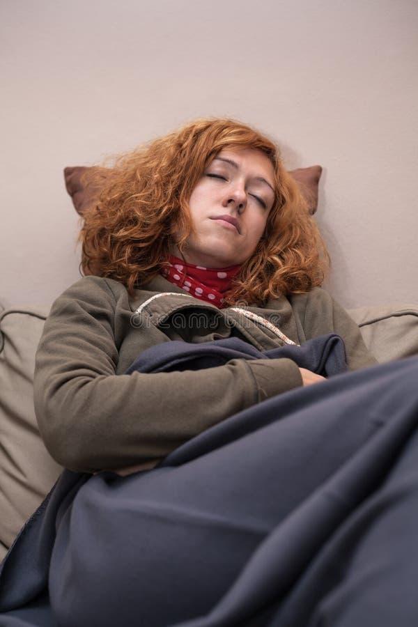 De slaap van de roodharigevrouw thuis stock afbeelding