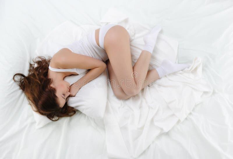 De slaap van de vrouw op het bed stock afbeelding