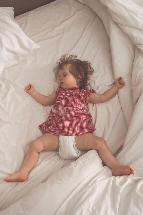 De slaap van het babymeisje op terug met open wapens en zonder fopspeen in een bed met witte bladen Vreedzame slaap in helder stock afbeeldingen