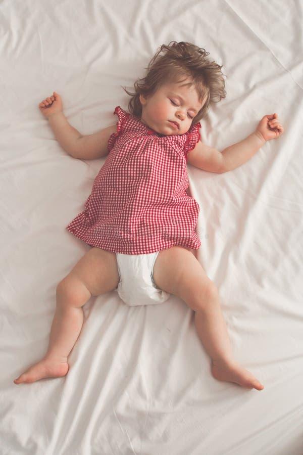 De slaap van het babymeisje op terug met open wapens en zonder fopspeen in een bed met witte bladen Vreedzame slaap in helder stock fotografie