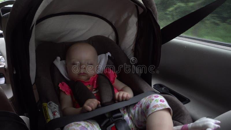 De slaap van het babymeisje in de zetel van de kindauto royalty-vrije stock afbeeldingen