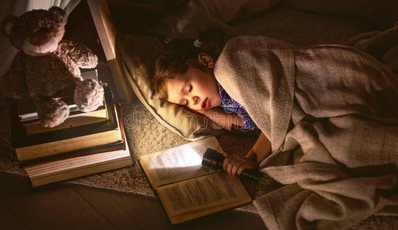 De slaap van het kindmeisje in tent met boek en flitslicht royalty-vrije stock afbeeldingen