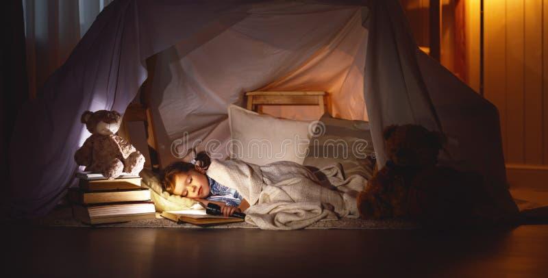 De slaap van het kindmeisje in tent met boek en flitslicht stock foto's