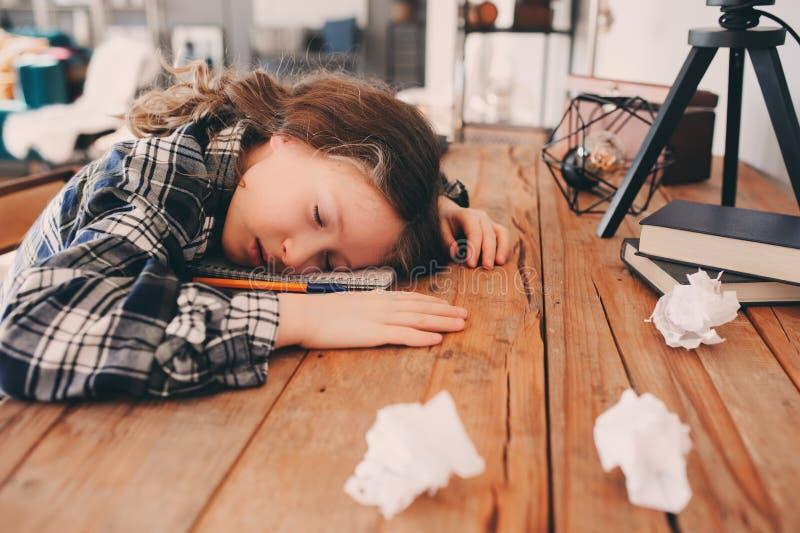 De slaap van het kindmeisje terwijl het doen van thuiswerk stock fotografie