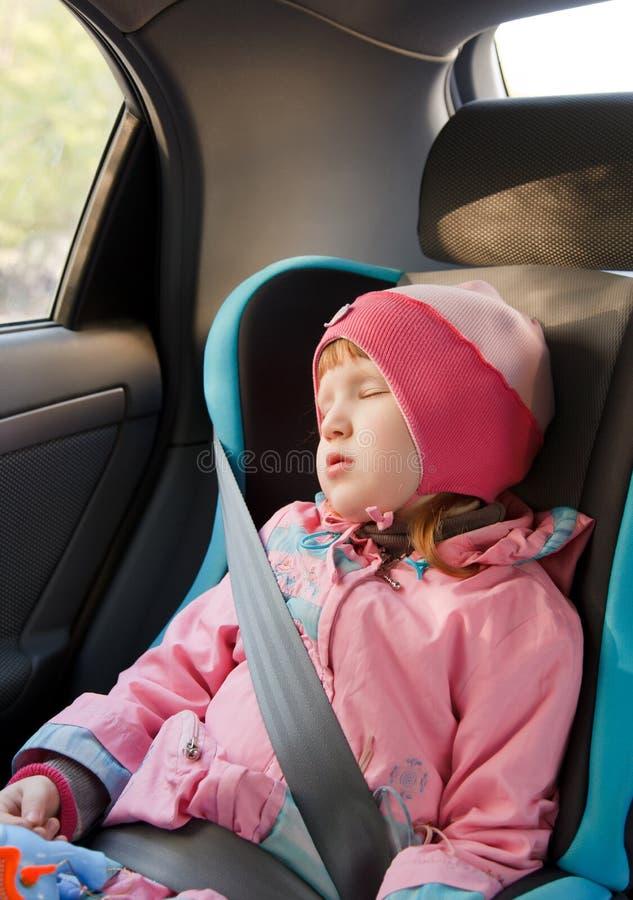 De slaap van het meisje in een auto stock afbeelding