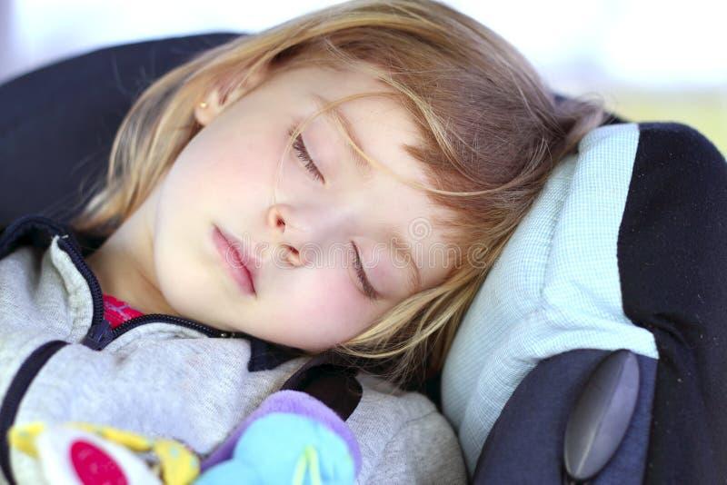 De slaap van het meisje op de veiligheidszetel van de kinderenauto royalty-vrije stock afbeelding