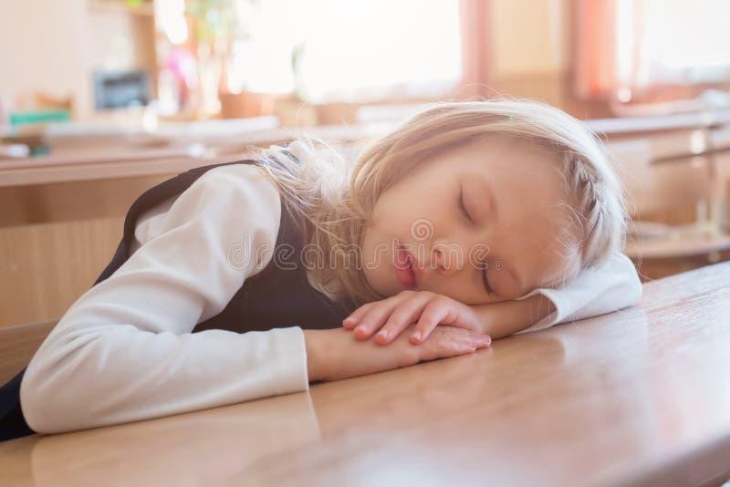 De slaap van het schoolmeisje op de school is slaap bij het bureau student Leerling het bestuderen royalty-vrije stock foto