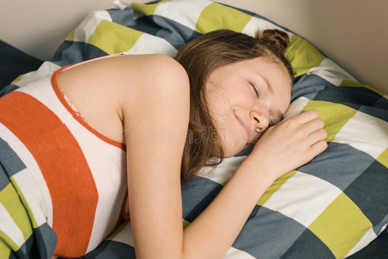 De slaap van het tienermeisje thuis in bed op hoofdkussen royalty-vrije stock foto's