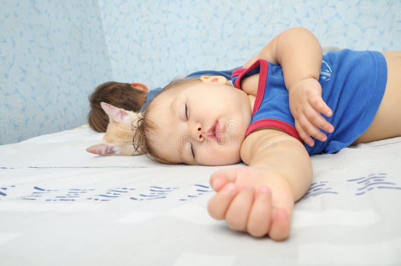 De slaapdag van het kindmeisje met broer en kat stock fotografie
