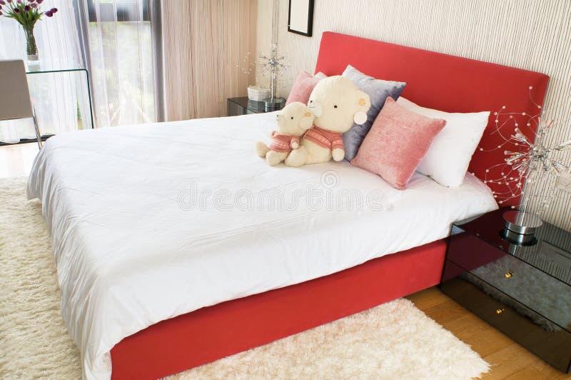 De slaapkamer van jonge geitjes met speelgoed op het bed stock afbeeldingen