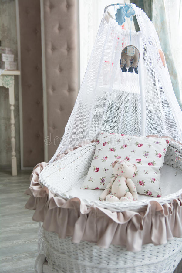 De slaapkamer van Retro binnenlandse kinderen met een rieten voederbak en teddy B stock foto