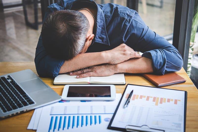 De slaapzakenman, Vermoeide hogere zakenmanslaap die lange werkdag hebben werkte zich op lijst in zijn bureau over royalty-vrije stock foto