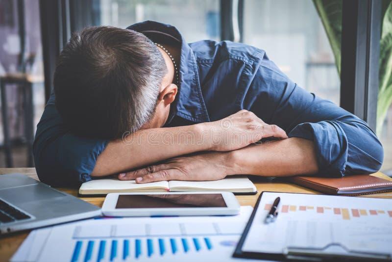 De slaapzakenman, Vermoeide hogere zakenmanslaap die lange werkdag hebben werkte zich op lijst in zijn bureau over royalty-vrije stock foto's